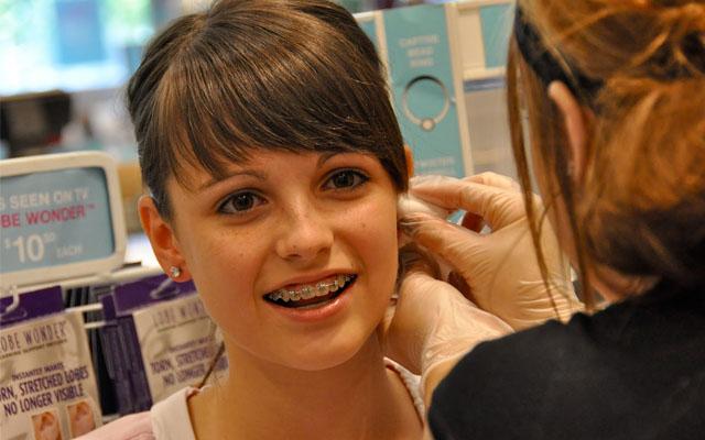 Teenager getting ears pierced
